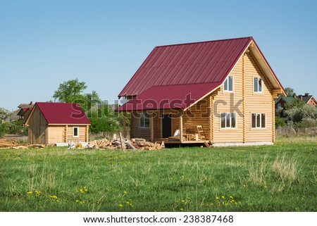 A small wooden house with iron roof and green lawn - stock photo