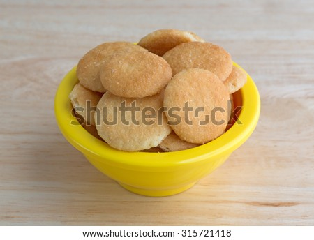 A small yellow bowl filled with vanilla flavored wafer cookies on a wood table top illuminated with natural light. - stock photo
