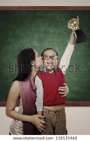A smart boy is raising a trophy while his mother is kissing him in the classroom
