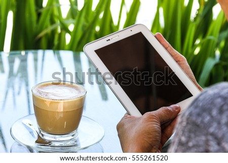 A smart phone and a cup of coffee on a wooden table