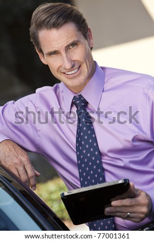 A smart successful businessman outside using a tablet computer - stock photo