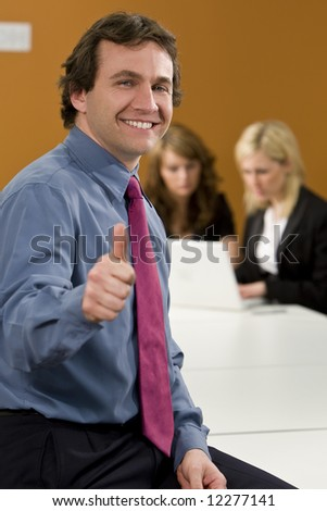 A smart young businessman gives a thumbs up while behind him two female colleagues work on a laptop