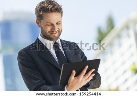 A smart young businessman with a beard using a tablet computer  - stock photo
