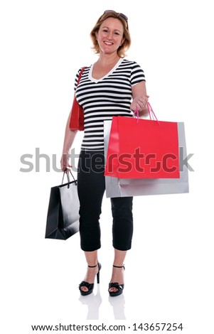 A smartly dressed mature woman holding shopping bags, isolated on a white background. - stock photo