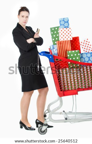 A smartly dressed woman shopping for gifts with a credit card and shopping cart on white.