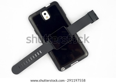 A smartwatch symbolicaly placed by a smartphone to emphasise the need of a smartphone for a smart watch to function. - stock photo