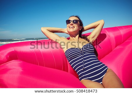 A smiley beauty holding her hands beyond the head sitting on the pink air boat and enjoying marvelous sunny and a bit windy weather on the beach.