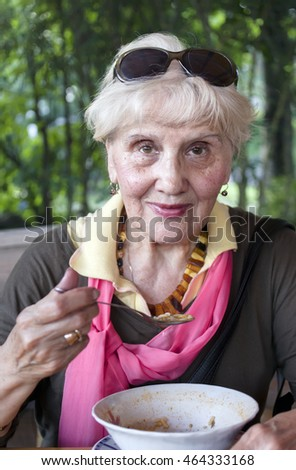A smiling aged woman having a soup, posing outdoors, vertical portrait