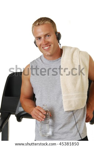 A smiling athletic man leaning against a treadmill with a bottle of water - stock photo