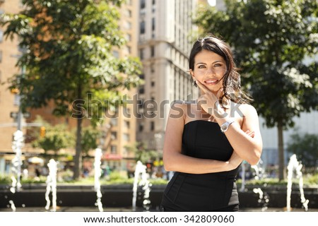 A smiling attractive woman with her hand to her chin. - stock photo