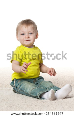 A smiling baby boy sits on the carpet