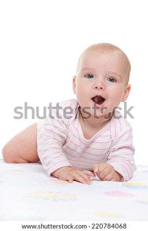 A smiling baby girl is crawling on the white towel