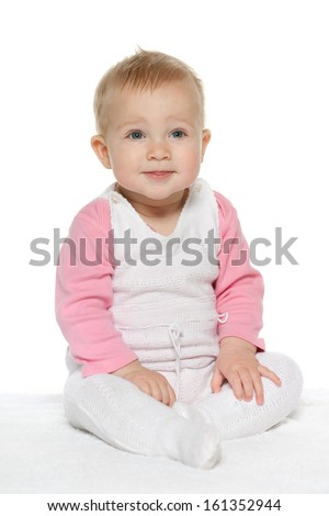A smiling baby girl sits on the white towel