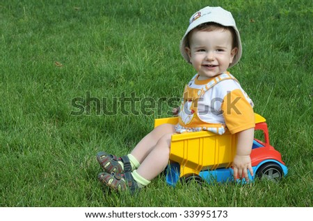 a smiling baby with a pacifier is sitting in the toy truck on the grass