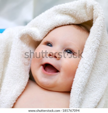 A smiling baby wrapped in quilt - stock photo