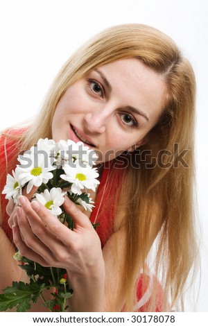 A smiling beautiful blonde in red with a bouquet of white chrysanthemums in her hands