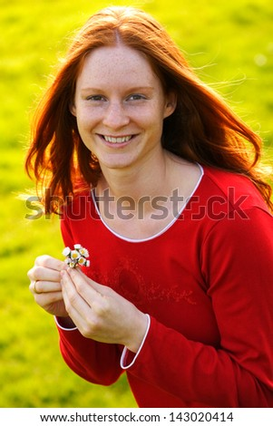 A smiling beautiful young Caucasian female holding some daisies in her hands and smiling at the camera. - stock photo