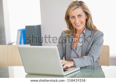 A smiling blonde businesswoman typing on a laptop in an office and looking at camera - stock photo