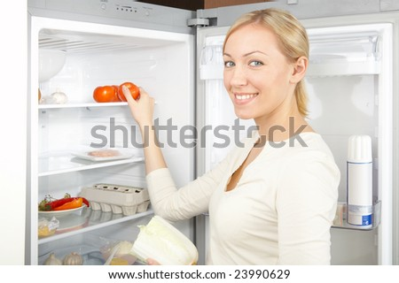 A smiling blonde takes a tomato from a refrigerator - stock photo