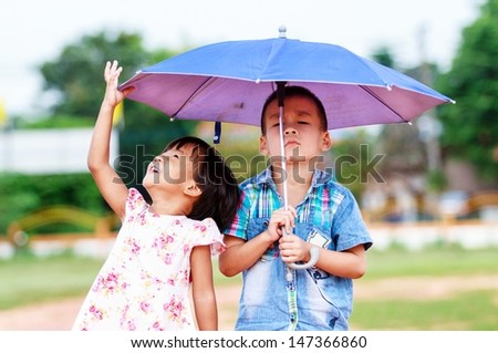 A smiling boy and a little girl in the park  - stock photo