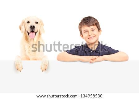 A smiling boy and Labrador retriever posing behind a blank panel - stock photo