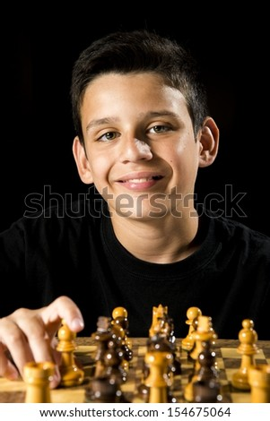 a smiling boy during a chess game.  - stock photo