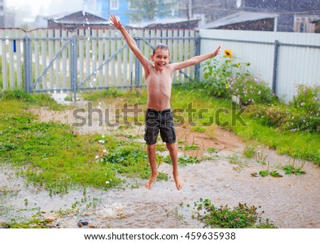a smiling boy jumping and having fun in summer rain. happy child during the warm summer rain. wet boy joyfully jumping in puddles under a downpour in the yard. the concept of a happy childhood