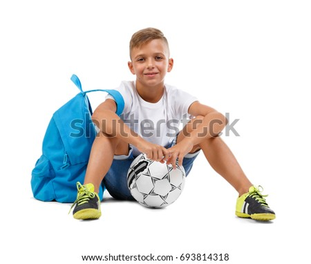 A smiling boy with a ball and a blue satchel sitting in a yoga pose. Happy child isolated on a white background. Sports concept.