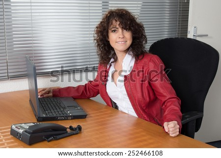A Smiling business woman in red, sitting satisfied at desk - stock photo