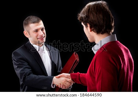 A smiling businessman shaking hands with his client - stock photo