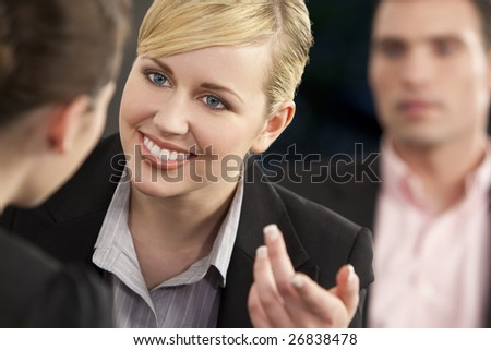 A smiling businesswoman and her two colleagues taking part in a happy business meeting - stock photo