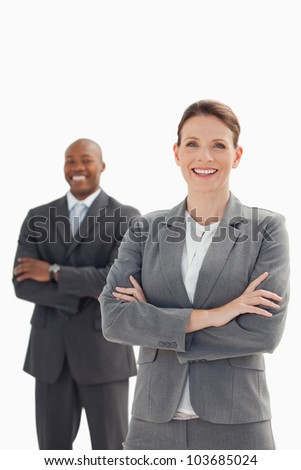 A smiling businesswoman stands in front of smiling businessman - stock photo