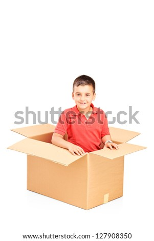 A smiling child in a cardbox isolated against white background