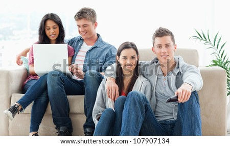 A smiling couple on the ground with a tv remote while another group sit on the couch together with a laptop - stock photo