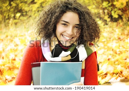 A smiling cute young female student with books in hand on the background of the autumn landscape. Female student in warm autumn. - stock photo