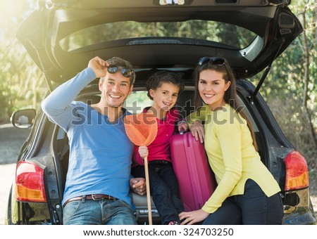 A smiling family looking at camera, they are sitting in the trunk of their car. They are leaving for the holidays. They are wearing colored pulls and holding a scoop net. The girl is seven years old