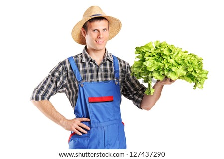 A smiling farmer holding a lettuce in his hand isolated on white background - stock photo