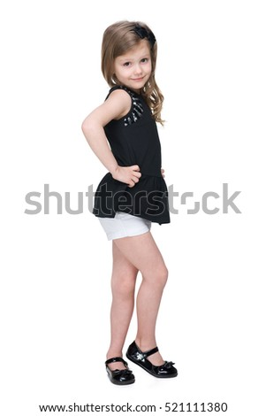A smiling fashion little girl is standing on the white background