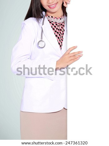 A smiling female doctor with a blank board, isolated on green background - stock photo