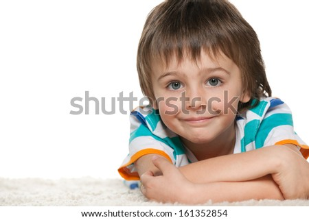 A smiling funny boy is lying on the white carpet - stock photo
