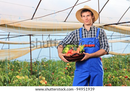 A smiling gardener holding a basket full of vegetables in a garden - stock photo