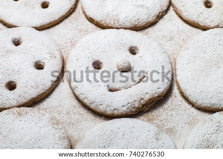 A smiling gingerbread sprinkled with sugar