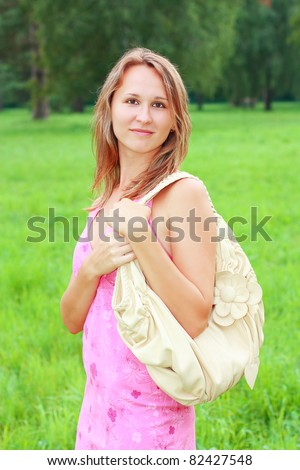 A smiling girl in a pink dress and a bag on his shoulder. Nature of the background