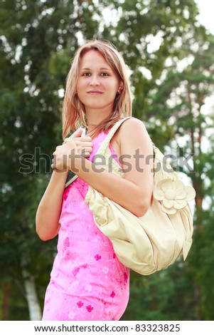 A smiling girl in a pink dress with a book in hand and a handbag on his shoulder - stock photo