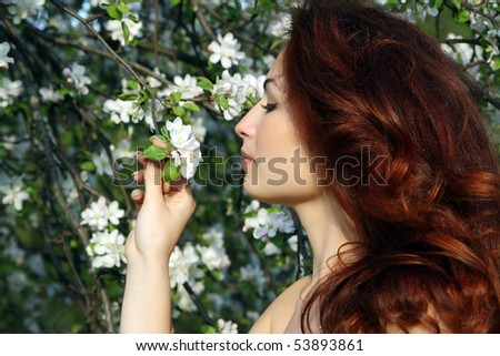 A smiling girl in apple-tree blossom - stock photo