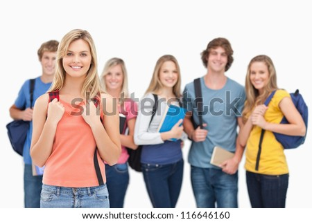 A smiling girl stands in front of her college friends as they all look at the camera - stock photo