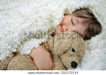 A smiling girl under a white blanket holding a soft toy dog - stock photo