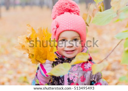 A smiling girl with a bouquet of yellow maple leaves on autumn forest background