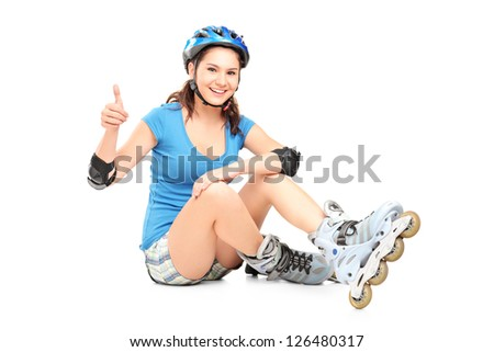 A smiling girl with roller skates giving a thumb up isolated on white background