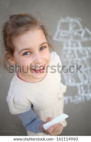 A smiling girl with white chalk in hand standing next to a hopscotch - stock photo